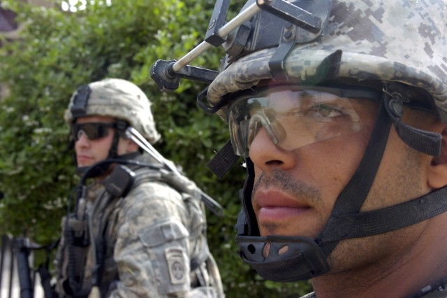 BAGHDAD - A National Policeman (right), assigned to 8th National Police Brigade, 2nd NP Division, and a Paratrooper assigned to the 2nd Battalion, 505th Parachute Infantry Regiment, 3rd Brigade Combat Team, 82nd Airborne Division, Multi-National Division-Baghdad look down a street in the neighborhood of Sumer al-Ghadier, located in the 9 Nissan district of eastern Baghdad during Operation Asfah Ramlyah, a combined clearance operation May 28. The combined forces teamed up to confiscated several weapons during the operation and check the area for improvised explosive devices.