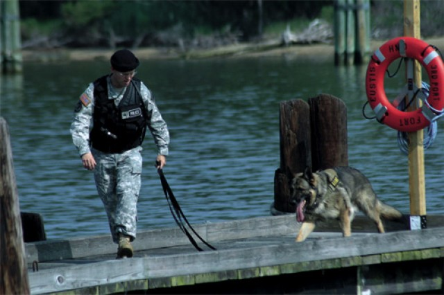 Sgt. Jonathan Drake and Military Working Dog Gudy inspect a pier for explosives at Fort Eustis' 3rd Port following the installation's annual anti-terrorism exercise, Vigilant Spear 2009 June 11. This year's event simulated an attack on Landing Support Vehicle Gen. Frank S. Bessom Jr. Eustis Soldiers and isntallation units and activities as well as civilian fire, police and emergency services from Gloucester, Hampton, Poquoson, James City County, Newport News and York County participated in the exercise. Naval Weapons Station Yorktown and Fort Story Garrison also provided assistance and resources for the simulation.