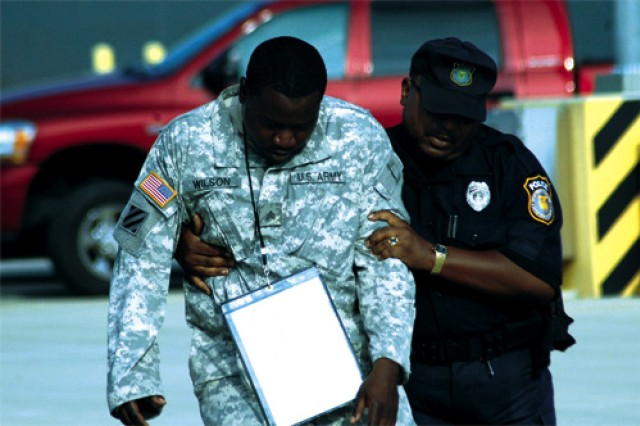 Department of the Army Civilian Police Officer Charles Washington escorts blast victim Sgt. Lee Wilson, 149th Transportation Detachment, 7th Sustainment Brigade, to an ambulance for medical attention.