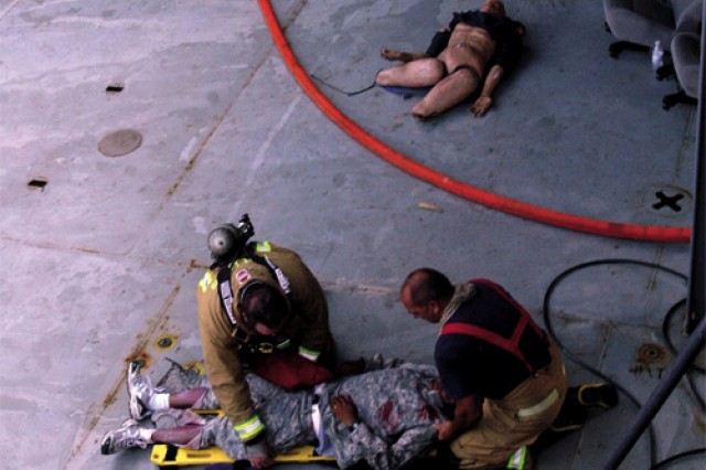 McKinley (left) and Eustis Fire Department Lt. David Wilder (right) secure a blast victim to a backboard for transport from the vessel to an ambulance waiting pierside.