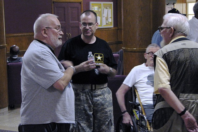 Master Sgt. Vince Norman, multi-instrument artist for 'Time Out,' interacts with veterans after the ensemble's performance at the Armed Forces Retirement Home in Washington, D.C.