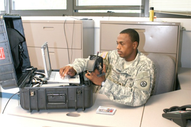 Spc. Darwynn McPherson, 688th Rapid Port Opening Element, Surface Deployment and  Distribution Command and Soldier for the third quarter,  performs maintenance checks on his  portable deployable kit. McPherson uses the PDK to scan equipment and containers during unit movements.