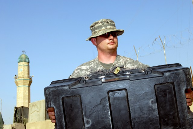 """BAGHDAD - As a minaret sounds the call to prayer in the background, Spc. Tyler Ring, an armorer, assigned to Headquarters and Headquarters Company, 2nd Squadron, 5th Cavalry Regiment, 1st Brigade Combat Team, 1st Cavalry Division, moves a box, May 26, in preparation for the transfer of Joint Security Station Sadr City back to the Government of Iraq. """"It's projected that we should be out of here in about 3 weeks,"""" said the Searcy, Ark., native. """"We gotta go somewhere else and continue our mission; we'll do whatever we gotta do to go home."""""""