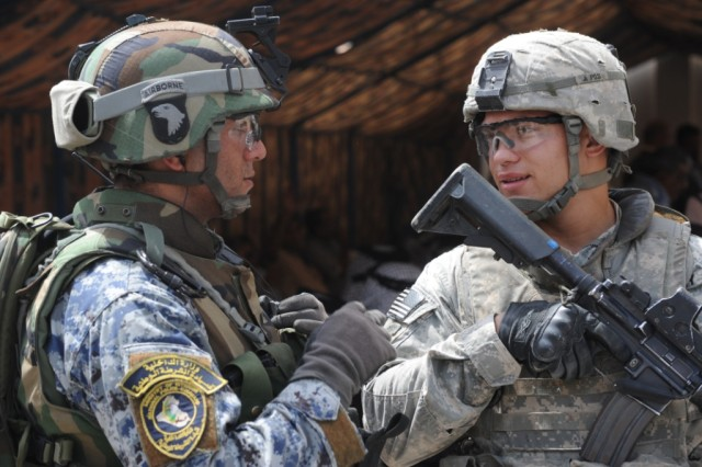 BAGHDAD - Sgt. Luis Zayas (right), of Cleveland, assigned to Headquarters and Headquarters Company, 2nd Battalion, 505th Parachute Infantry Regiment, 3rd Brigade Combat Team, 82nd Airborne Division, Multi-National Division-Baghdad, talks to a National Policeman during the opening of the al-Ameen Police Station, May 27, in the 9 Nissan district of eastern Baghdad. Iraqi's Interior Minister, Jawad al-Bolani, and senior U.S. and Iraqi security officials in the district were also in attendance for the ceremony.