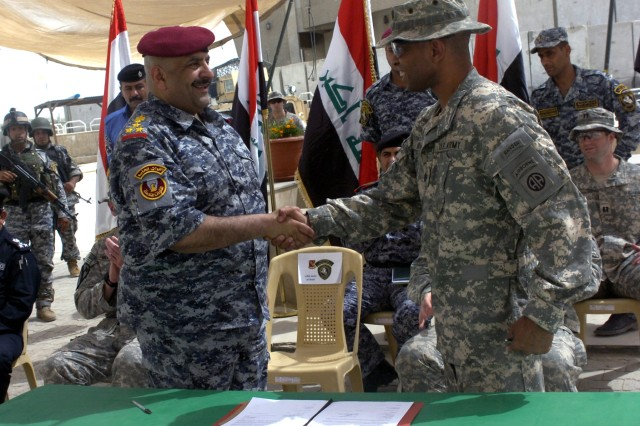 BAGHDAD - Iraqi Brig. Gen. Amer Khames Hameed (left), commander of the 1st Brigade, 1st National Police Division, shakes hands with Lt. Col. William E. McRae, of Cleveland, commander of 1st Battalion, 319th Airborne Field Artillery Regiment, 3rd Brigade Combat Team, 82nd Airborne Division, Multi-National Division-Baghdad, after signing a document officially transferring full control of Joint Security Station Babil to the Iraqi Security Forces, May 26, in the al-Karradah district of eastern Baghdad. The JSS is now the home of the National Police's 3rd Regiment, 1st NP Bn., 1st NP Bde.