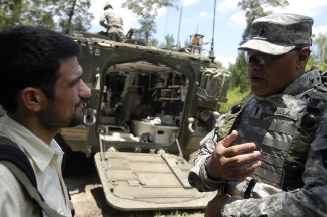 Chaplain (1LT) Folauga Tupuola, chaplain for the 4th Battalion, 9th Infantry Regiment, 4th Stryker Brigade Combat Team , 2nd Infantry Division, speaks with an Iraqi interpreter during the Unit Ministry Team situational training exercise at Fort Polk's Joint Readiness Training Center, June 15.