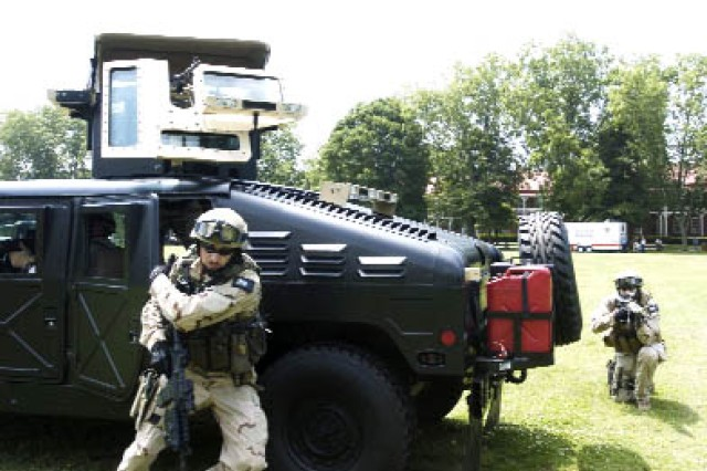 A member of the Team TAC, a civilian air soft tactical recreation team based out of Cleveland, Ohio, dismounts a hummer to provide security during a re-enactment of a special forces extraction of a wounded Soldier.