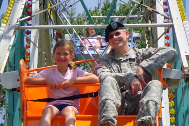 Marissa Huntley, 7, and her uncle, Army Ground Forces Band percussionist Sgt. James Broeker, enjoy the view of Hedekin Field from the Ferris wheel.