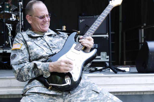 """Sgt. 1st Class John Verner rocks his guitar during a cover of """"Freebird"""" by Lynyrd Skynyrd. Verner is the guitarist of the """"Loose Cannons,"""" the U.S. Army Ground Forces rock band. The band played sets during the Army birthday celebration Tuesday on Fort McPherson to entertain the audience."""