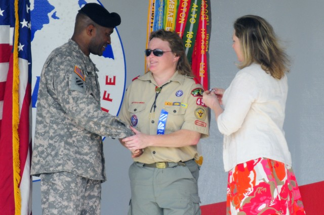 Command Sergeant Major Jesse Andrews, 3rd Infantry Division command sergeant major, and Ginger Cucolo, award Michelle Burkhard with the Marne Spirit Award at Cottrell Field, June 11. Burkhard volunteers as scoutmaster for Boy Scout Troop 454.