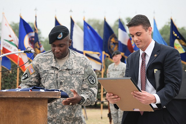Jonathan Huhn, Senator John Cornyn's local legislative director, presents the U.S. Flag flown over the nation's capitol to Command Sgt. Maj. Howard Riles, Fort Sam Houston and U.S. Army Medical Department Center and School in honor of the Army's birthday and to the Noncommissioned Officers Corps in recognition of 2009 as the Year of the NCO during the Army Birthday ceremony at Fort Sam Houston.