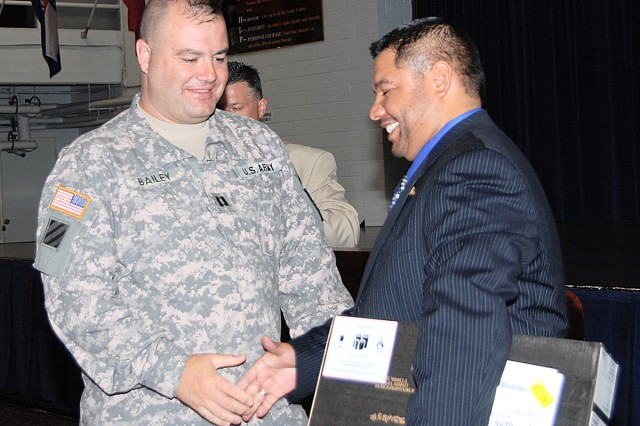 Capt. Ronald Bailey (left), A Company, Warrior Transition Battalion, accepts a laptop from Rudy Guerra, employment advisor, U.S. Department of Labor/Veteran's Employment and Training Service in a graduation ceremony held June 12 at Fort Sam Houston Army Community Service for the Transition Training Academy. Bailey was one of 17 wounded warriors to graduate from the TTA, and receive a certificate and a laptop.