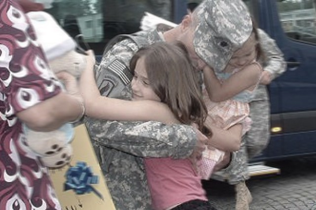 Lt. Col. Jim Ryan, currently with the Office of the Deputy Chief of Staff, G-4, embraces his two daughters after a 15-month deployment in Afghanistan with the 173rd Brigade Support Battalion.