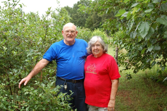 """COL(R) Jack and Anne Story stand in  front of a row of blueberry bushes.  Anne said Soldiers who saw last year's Bayonet article spent the day with Jack after redeploying from Iraq.  """"They just wanted to unwind.  And this was the place."""""""