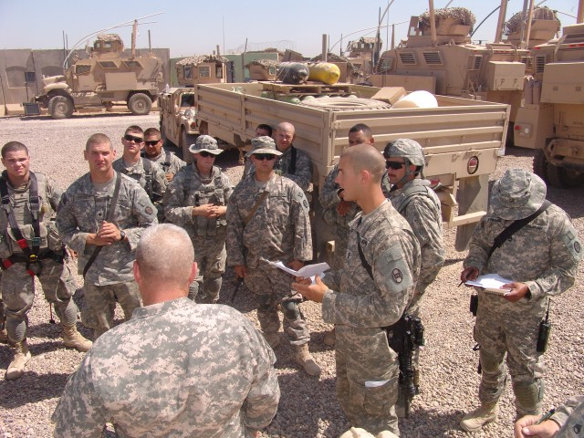 BAGHDAD - First Lt. Matthew Mason (right), a platoon leader with Company B, 120th Combined Arms Battalion, 30th Heavy Brigade Combat Team, Multi-National Division-Baghdad, briefs his Soldiers on the day's mission at the unit's motor pool on Forward O...