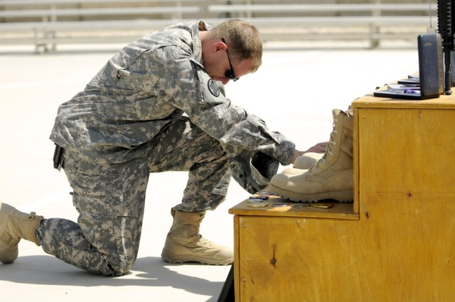 BAGHDAD-Maj. Toby Clifton, of Headquarters and Headquarters Company, 30th Heavy Brigade Combat Team, kneels in front of a memorial to the three brigade Soldiers killed by a bomb, May 21.  The May 29 memorial service, at Forward Operating Base Falcon,...