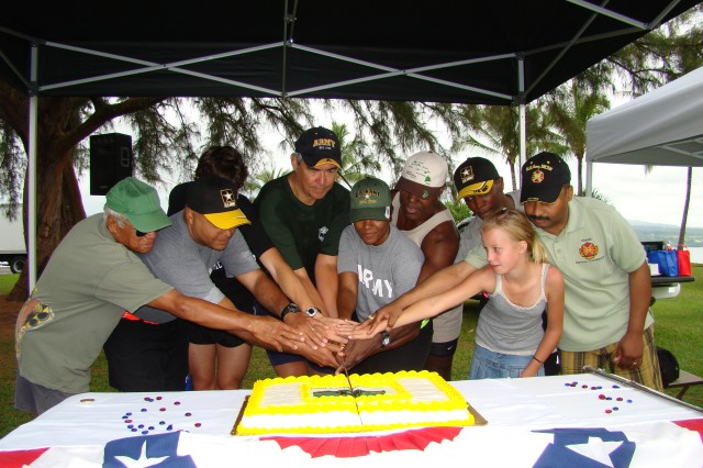 HILO, Hawaii - Bill Moore (center), Big Island's Civilian Aide to the Secretary of the Army (CASA), along with local runners, walkers and Pohakuloa Training Area staff, cuts the post-run cake, in celebration of the Army's 234th birthday, June