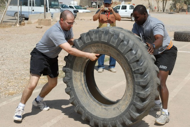 Sgt. Ricky Ford (right), a Tyler, Texas, native and a signal specialist, and Sgt. Robert Shaw, an Elmira, N.Y., native and a Human resources specialist, both with Headquarters and Headquarters Troop, 4th Battalion, 9th Cavalry Regiment, 2nd Brigade Combat Team, 1st Cavalry Division, flip a tire May 24 at Forward Operating Base Warrior's Mountain Warrior Gym as part of one of the challenges that comprised Commander's Cup. Both the Army and Air Force had teams that participated during the competition.