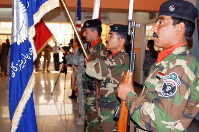 A mix of Iraqi Police and U.S. Soldiers act as the color guard during a ceremony May 19 at the Provincial Joint Control Center in Kirkuk city, Iraq, which honored four IP and one Kirkuk resident who stopped a would-be suicide bomber from detonating himself in a mosque in downtown Kirkuk city.