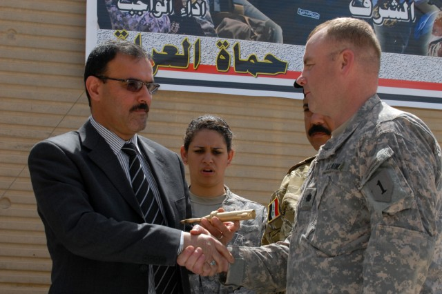 BAGHDAD - Lt. Col. John Vermeesch (right), a Roscommon, Mich., native and commander of 1st Battalion, 18th Infantry Regiment, 2nd Brigade Combat Team, 1st Infantry Division, shakes hands with Samir Hadad, the secretary director for the prime minister, after giving him the key to Joint Security Station Hurriyah, May 30.