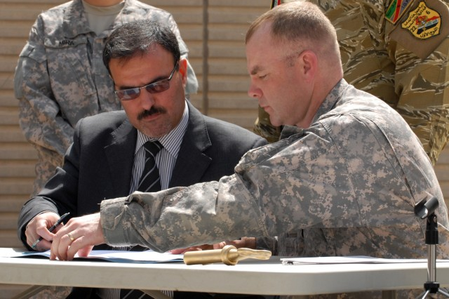"""BAGHDAD -- Lt. Col. John Vermeesch (right), a Roscommon, Mich., native and commander of 1st Battalion, 18th Infantry Regiment, 2nd Brigade Combat Team, 1st Infantry Division, prepares to sign transfer contracts with Samir Hadad, the secretary director for the prime minister, at Joint Security Station Hurriyah, May 30.  """"This is a historic time for Hurriya, for Baghdad and all of Iraq and I am proud to be a part of it,"""" said Vermeesch."""