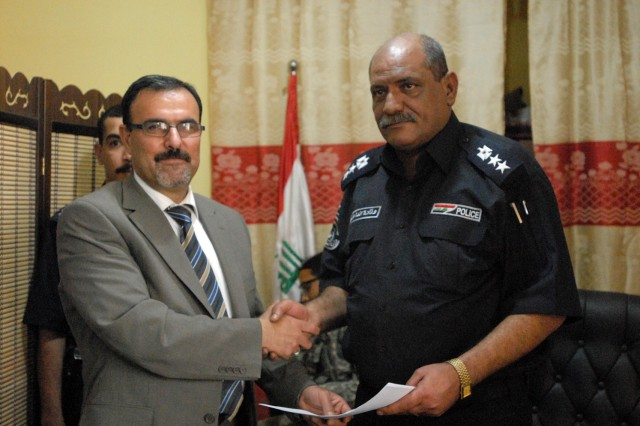 "BAGHDAD- Iraqi Col. Mohmad Laeftah Fleh (right), the director of Shaab Police Station, shakes hands with the Prime Minister of Iraq's representative, after signing for the responsibility of Joint Security Station Shaab, May 28. JSS Shaab is one the first of eight JSS's in the Baghdad area to have responsibility transferred back to the Government of Iraq. The 1st ""Ironhorse"" Brigade Combat Team, 1st Cavalry Division was also successful in transferring JSS Adhamiyah. The process of transferring responsibility of JSS's will be completed no later than June. 30."