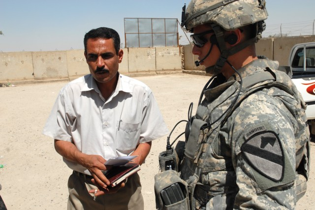 "BAGHDAD - First Lt. Joe Zoretic (right), of Nashville, Tenn., a platoon leader assigned to Battery B, 1st Battalion, 82nd Field Artillery Regiment, 3rd Brigade Combat Team, 82nd Airborne Division, talks with a council member in the town of Jisr Diyala here, May 29. ""The first consideration is security and second is getting to the point where you've already had a relationship with these local leaders and the National Police and getting them to where they can trust the new guys coming in and they don't feel like you're leaving them high and dry,"" said Zoretic."