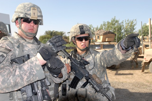 "BAGHDAD - First Lt. Joe Zoretic (right) of Nashville, Tenn., a platoon leader assigned to Battery B, 1st Battalion, 82nd Field Artillery Regiment, 3rd Brigade Combat Team, 82nd Airborne Division, (right) talks with Cpt. Robert Reece, commander of Battery A, 1st Bn., 82nd FA Regt., 3rd BCT, 82nd Airborne Div., during a reconnaissance of a field where a weapons cache was found weeks earlier in Jisr Diyala. ""Battery B showed us where three weeks ago they found a cache and let us know that they had found weapons in the area before to draw it to our attention and make sure we know this is an area where weapons were kept and what to look for in another area,"" said Reece, a native of Seguin, Texas."