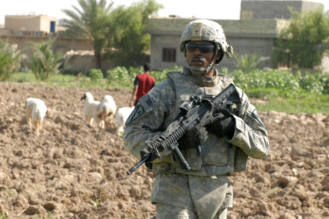 BAGHDAD - Staff Sgt. Harold Waterman, an artilleryman assigned to Battery B, 1st Battalion, 82nd Field Artillery Regiment, 3rd Brigade Combat Team, 82nd Airborne Division, pulls security during a reconnaissance of a field in Jisr Diyala where a weapons cache was found three weeks earlier. Waterman, a native of Terry, Miss., was helping introduce Soldiers of Btry. B's sister unit, Btry. A, to the Jisr Diyala area.