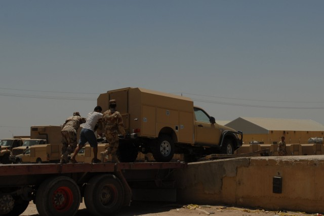 Iraqi army soldiers assist a civilian contractor in pushing a truck from a flatbed trailer, May 30, at Taji National Supply Depot. The depot is the Iraqi Army's national level logistics and supply center.