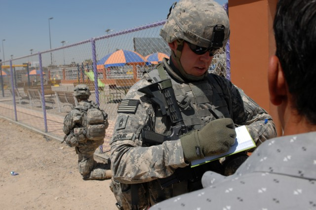 BAGHDAD - Master Sgt. Robert LaTour, a civil affairs team leader from Tacoma, Wash., assigned to Company B, 448th Civil Affairs Battalion, 1st Brigade Combat Team, 1st Cavalry Division, takes notes and asks questions from local community members about a Coalition forces funded playground behind him in Sadr City, May 31.