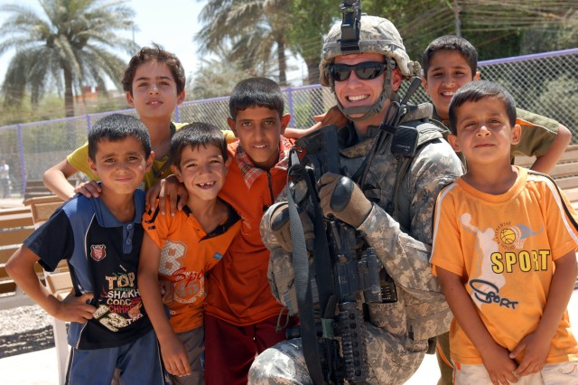 """BAGHDAD - Seattle native, Staff Sgt. Matthew Bissell, a civil affairs team sergeant assigned to Company B, 448th Civil Affairs Battalion, 1st Brigade Combat Team, 1st Cavalry Division, takes a moment during a project assessment to smile with Iraqi children at a recently finished playground in Sadr City, May 31. """"Sadr City looks better now,"""" said Bissell. """"There are more parks and everything's landscaped which gives them more a sense of pride in their neighborhood."""""""