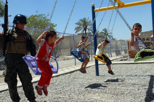 BAGHDAD - Iraqi Army Pvt. Abass Fadal Juwad, an infantryman assigned to 3rd Battalion, 44th Brigade, 11th Iraqi Army Division, takes a moment to play with some Iraqi children while on patrol with Soldiers of 2nd Battalion, 5th Cavalry Regiment, 1st Brigade Combat Team, 1st Cavalry Division, at a Coalition forces-funded playground in Sadr City, here, May 31. The official opening of the park, which took about a month and half to complete, is scheduled for sometime in early June.