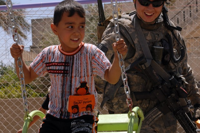"""BAGHDAD - """"It makes my day when I see a smile on a kids face,"""" said Spc. Edward Suarez, a tanker from Phelan, Calif., assigned to Company B, 2nd Battalion, 5th Cavalry Regiment, 1st Brigade Combat Team, 1st Cavalry Division, as he shares a smile with an Iraqi child while on a CF funded playground assessment in Sadr City, here, May 31. """"It helps kids when they see us building stuff for them,"""" added Suarez. """"It helps them see that they shouldn't be afraid of us."""""""
