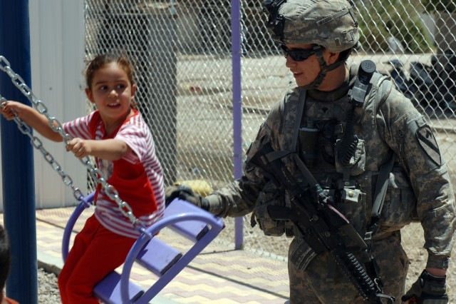 """BAGHDAD - Spc. Edward Suarez, a tanker from Phelan, Calif., assigned to Company B, 2nd Battalion, 5th Cavalry Regiment, 1st Brigade Combat Team, 1st Cavalry Division, gives a push to an Iraqi girl at a recently finished playground funded by CF in Sadr City, here, May 31. """"I like kids,"""" said Suarez, a native of Phelan, Calif. """"When I'm able to get out there and play with the kids, it feels good and helps brighten the mood."""""""