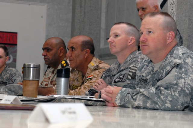 VICTORY BASE COMPLEX, Iraq - Command Sgt. Maj. Michael Woods (right), of Pine Bluff, Ark., and Lt. Col. Geoffrey Stevens (second from right), from Melrose, Mass., both assigned to 79th Ordnance Battalion, Task Force Troy, listen to a speaker at the Baghdad Iraqi Security Forces Explosive Ordnance Disposal Conference here, June 2. The purpose of the conference was to plan for future operations in Baghdad under the Status of Forces Agreement, according to Stevens.