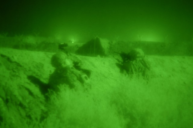 TAJI, Iraq - As seen through a night vision lens, two Soldiers from Company B, 1st Battalion, 112th Infantry Regiment, based in Corry, Pa., scan the Iraqi countryside north of Camp Taji in the early morning hours of May 31. The Pennsylvania National Guard Soldiers, with the 56th Stryker Brigade Combat Team, deter possible placement of weapon caches by observing the area after it is lighted by illuminating artillery rounds fired from Camp Taji.