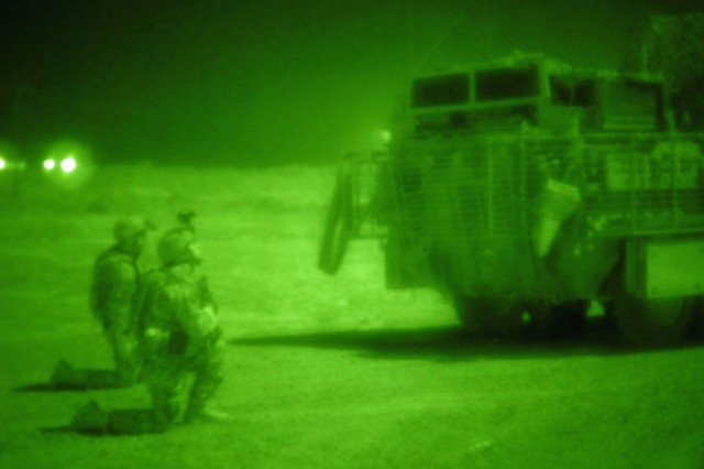 TAJI, Iraq - From behind their Stryker vehicle, Sgt. Ben Behringer  (at right) of Lake City, Pa., Company B, 1st Battalion, 112th Infantry Regiment, 56th Stryker Brigade Combat Team, and another Soldier scan the Iraqi countryside north of Camp Taji in the early morning hours, May 31. The Pennsylvania National Guard Soldiers, seen here through a night vision lens, deter placement of weapon caches by observing the area with help from illumination artillery rounds fired from Camp Taji.