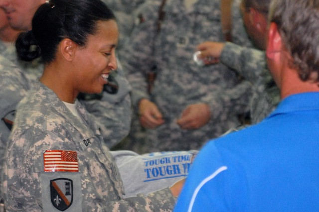 BAGHDAD - Cpt. Yvonne McFarland-Davis (left), of the 225th Engineer Brigade, shows her excitement after receiving a signed T-Shirt from the UCLA head football coach, Rick Neuheisel, during a meet and greet at the Engineer Chapel on Camp Liberty, Baghdad, June 1. Coach Neuheisel, with his fellow college football coaches: Mack Brown of the University of Texas, Troy Calhoun of the Air Force Academy, Jim Grobe of Wake Forest University, Mack Brown of the University of Texas, Jim Tressel of Ohio State University, and former University of Auburn coach Tommy Tuberville, took time out of their busy schedules to visit with deployed troops overseas answering questions, signing autographs and show their overall support for the U.S. troops.