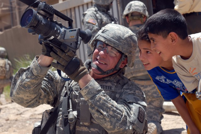 """BAGHDAD - """"Everyone knows Iraqi children love the camera,"""" said Sgt. Erik Fardette, a video broadcaster from Mililani, Hawaii, assigned to the 211th Mobile Public Affairs Detachment, Multi-National Division-Baghdad, as he takes a minute to interact with two Iraqi children while on patrol in Sadr City, May 31. """"I have kids around the same age, interacting with Iraqi children reminds me of home. These kids were excited to look through the viewfinder just like mine would be,"""" added Fardette. """"Even though we're in a combat zone it's nice to be able to share light moments like this."""""""