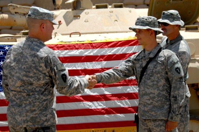 BAGHDAD - Col. Lee Henry (left), commander of 56th Infantry Brigade Combat Team, congratulates Spc. Timothy Vaden after reciting the oath of enlistment during a re-enlistment ceremony at Camp Victory, Iraq, June 2. Vaden, from Saginaw, Texas and new father, re-enlisted for an additional six years in the Texas Army National Guard.