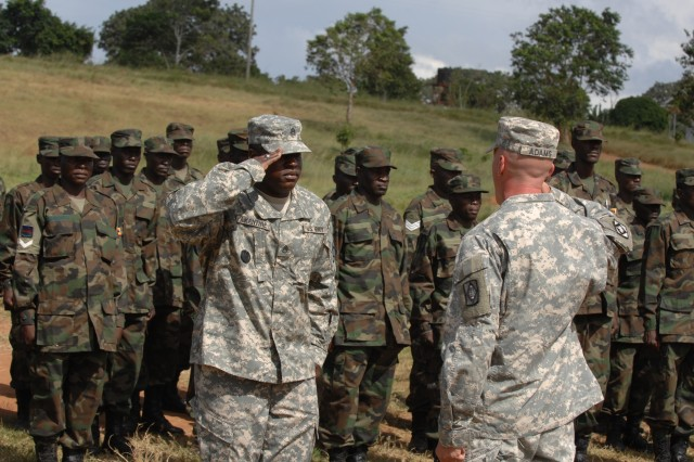 Staff Sgt. Andre Amantine of 2nd Battalion, 18 Field Artillery Regiment, out of Camp Lemonier, Djibouti, salutes Sgt. 1st Class Cary Adams - course Sergeant Major, during a 15-week counter-terrorism course, June 16, 2009, at Camp Kasenyi, Uganda. More than 100 Ugandan soldiers graduated from this CJTF-HOA-supported course, which covered topics such as individual movement techniques, troop landing procedures, land navigation, first aid, identifying improvised explosive devises, and more.