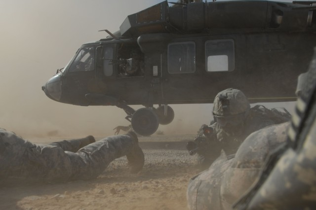 TAJI, Iraq - Staff Sgt. Craig Stevens (center), of Pottsville, Pa., with Headquarters and Headquarters Company, 1st Battalion, 112th Infantry Regiment, maneuvers through a cloud of dust to get into position between two other Soldiers, June 3, after dismounting the departing UH-60 Blackhawk helicopter. The 56th Stryker Brigade Combat Team Soldiers air assaulted into the desert near Nubai, northwest of Taji, along with Iraqi Army Soldiers to conduct searches for possible weapons caches.