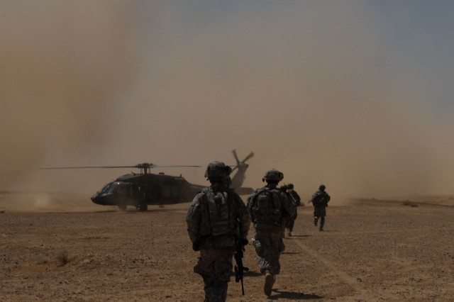 TAJI, Iraq - Soldiers of 1st Battalion, 112th Infantry Regiment, 56th Stryker Brigade Combat Team move toward a waiting UH-60 Blackhawk helicopter, June 3, to leave a search site in the Iraqi desert near Nubai. The Pennsylvania Guardsmen worked with Soldiers of the Iraqi Army's 2nd Battalion, 37th Brigade to search for possible weapons caches after air assaulting into the area.