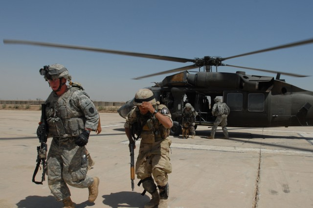 TAJI, Iraq - Spc. Elam Scott (left), of Pottstown, Pa., Headquarters and Headquarters Company, 1st Battalion 112th Infantry Regiment, and an Iraqi Army Soldier make their way off a helipad at Camp Taji, June 3, at the end of a mission. The 56th Stryker Brigade Combat Team Soldiers worked with IA Soldiers to search for weapons caches after air assaulting into the Iraqi desert near Nubai, northwest of Taji.