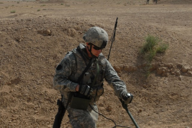 """TAJI, Iraq - Sgt. Brian Reger, of Ellicott City, Md., 856th Engineer Company, 56th Stryker Brigade Combat Team, runs a metal detector over a suspected weapons cache site, June 3. """"Independence"""" Soldiers worked with Iraqi Army Soldiers to search an area northwest of Taji which has been used in the past for hiding weapons."""