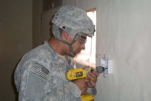 BAGHDAD - Pfc. Andrew Seymour, carpentery/masonry specialist, 46th Engineer Combat Battalion (Heavy), 225th Engineer Brigade, of Escanaba, Mich. prepares an electrical outlet in the Aid Station at Patrol Base Yusifiyah.