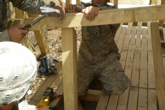 BAGHDAD - Carroll, Iowa native, Spc. Cory Riesenberg, a carpentery/masonry specialist, 46th Engineer Combat Battalion (Heavy), 225th Engineer Brigade, holds a railing in place outside the tactical operating center at Patrol Base Yusifiyah, while waiting for it to be secured in place.