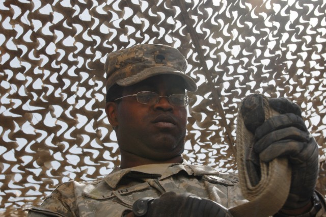 """BAGHDAD - """"A lot of them realize when their truck has a flat, they come to us,"""" said Spc. Ariel Lain, a mechanic assigned to B Company, 2nd Battalion, 5th Cavalry Regiment, 1st Brigade Combat Team, 1st Cavalry Division, as he coils a tow strap in the motor pool of Joint Security Station Sadr City, here, May 31. """"We keep those guys mission ready lifting MRAPs and humvees, changing out tires."""""""