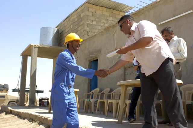 A gift for his exceptional work on the project and during training is presented to one of the distinguished students, during the graduation ceremony May 24. The students' training started in December 2008 and continued while they were building the Tal Abtha Road.